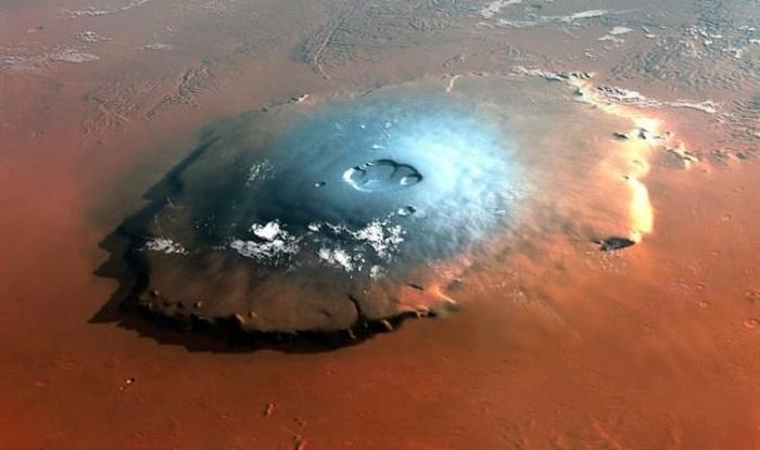 Woda na Marsie. Na fotografii zarejestrowane pokłady zamarzniętych brył na Olympus Mons, wznoszącej się na 25 km. Źródło: express.co.uk.